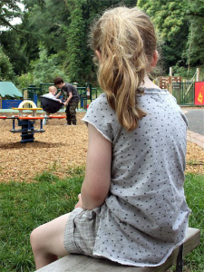Divorce and special needs children: picture of back of girl sitting alone in playground