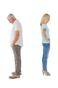 photo of man and woman standing apart with their backs to each other and heads down