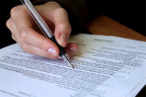 spousal support: photo of person's hand holding a pen and filing out documents