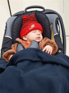 car seat safety: photo of baby dressed in heavy fur coat buckled into child safety seat