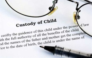 Joint Custody -- photo of pen and corner of eyeglasses lying on a Child Custody agreement