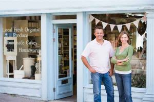Protecting family-owned business from divorce - photo of couple standing outside storefront of grocery business