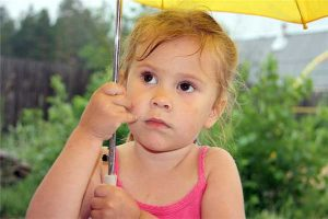 divorce precautions - photo of young girl in pink top holding yellow umbrella