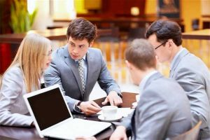 Divorce mediation: photo of three men and one woman sitting at conference table with laptop and coffee cup
