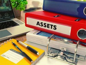 "Mediation Financial Issues - photo of notebooks labeled ""assets"", eyeglasses, pens, and laptop on a table"