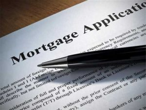 Photo of pen lying on top of mortgage application illustrating need to refinance after divorce